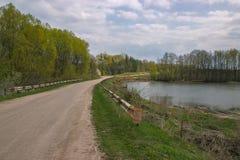 foto av den lantliga vägen med sjön Arkivfoton