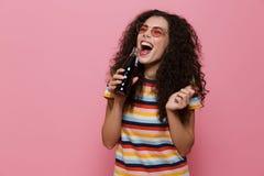 Foto av den lyckliga kvinna20-tal med lockigt hår som dricker sodavatten från glas royaltyfri foto