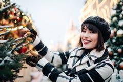Foto av den lyckliga kvinnan nära den målade julgranen på gatan royaltyfria bilder