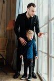 Foto av den lyckliga mannen och hans sonsammanträde vid fönstret arkivbild