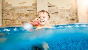 Foto av den lyckliga skratta och le pysen som spelar med leksaker och inomhus l?r simning i simbass?ng royaltyfria foton