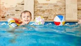 Foto av den lyckliga skratta och le pysen som spelar med leksaker och inomhus l?r simning i simbass?ng royaltyfria bilder