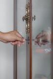 Foto av den manliga handen som sätter kabinetttangent in i ytterdörrlåset av c Royaltyfri Foto