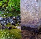 Foto av den near konkreta kolonnen för mörkt vattenflöde Royaltyfria Foton