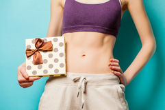 Foto av den perfekta slanka kvinnliga kroppen med den gulliga gåvan i handen på arkivbild