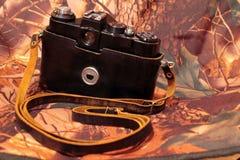 Foto av den retro kameran på kamouflaget Royaltyfri Bild