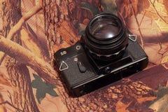 Foto av den retro kameran på kamouflaget Arkivbild
