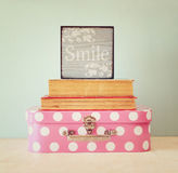 Foto av den rosa resväskan med polkadots och bunt av böcker över trätabellen, retro stilbild Royaltyfri Bild