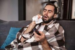 Foto av den sjuka man30-tal som slås in i filten som dåligt är, medan sitta på soffan i lägenhet royaltyfri fotografi