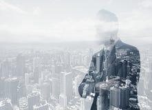 Foto av den stilfulla vuxna affärsmannen som bär den moderiktiga dräkten Dubbel exponering, modern stadsbakgrund för panoramautsi royaltyfri fotografi