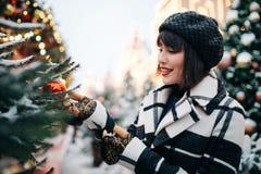 Foto av den unga brunetten nära den målade julgranen på gatan arkivfoto