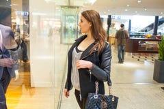 Foto av den unga glade kvinnan med handväskan på bakgrunden av sh Royaltyfria Bilder
