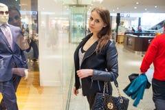 Foto av den unga glade kvinnan med handväskan på bakgrunden av sh Royaltyfri Foto