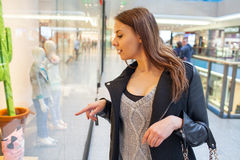 Foto av den unga glade kvinnan med handväskan på bakgrunden av sh Royaltyfria Foton