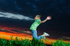 Foto av den unga pojkebanhoppningen och lyftahänder Royaltyfria Bilder