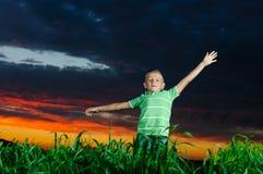 Foto av den unga pojken som lyfter händer Royaltyfri Fotografi