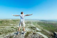 Foto av den unga stiliga allvarliga mannen som är stående tillbaka till kameran över berg och att se åt sidan Royaltyfri Bild