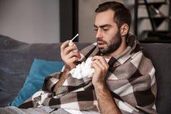 Foto av den upprivna man30-tal som slås in i filten som dåligt är, medan sitta på soffan i lägenhet arkivfoton