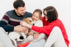 Foto av den vänliga familjen att omfamna sig och smickra deras för att göra arkivfoton