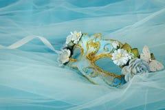 Foto av elegant och delikat guld och den blåa venetian maskeringen över silke- och chiffongbakgrund royaltyfri foto
