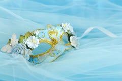 Foto av elegant och delikat guld och den blåa venetian maskeringen över silke- och chiffongbakgrund arkivbilder