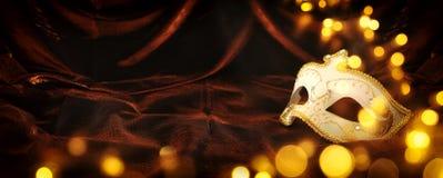 Foto av elegant och delikat guld, vit venetian maskering över mörk sammet och siden- bakgrund royaltyfria foton