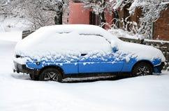 Foto av en bil som täckas i ett tjockt lager av snö Följder av tungt snöfall arkivfoton