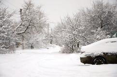 Foto av en bil som täckas i ett tjockt lager av snö Följder av tungt snöfall royaltyfria bilder