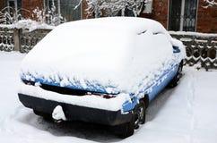 Foto av en bil som täckas i ett tjockt lager av snö Följder av tungt snöfall royaltyfria foton