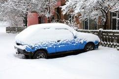 Foto av en bil som täckas i ett tjockt lager av snö Följder av tungt snöfall arkivfoto