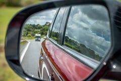 Foto av en bilspegel under ett drev arkivfoto