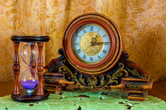 Foto av en gammal klocka och sandglass på brun bakgrund Arkivbild