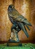 Foto av en gammal statyett av falken på brun bakgrund Arkivbilder