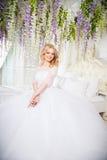 Foto av en härlig blond brud i en lyxig bröllopsklänning i inre Fotografering för Bildbyråer
