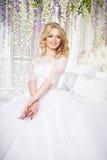Foto av en härlig blond brud i en lyxig bröllopsklänning i inre Arkivbilder