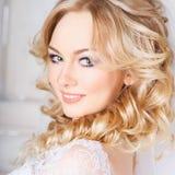 Foto av en härlig blond brud i en lyxig bröllopsklänning i inre Arkivfoto