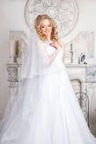 Foto av en härlig blond brud i en lyxig bröllopsklänning i inre Royaltyfria Bilder