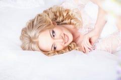 Foto av en härlig blond brud i en lyxig bröllopsklänning i inre Royaltyfri Fotografi
