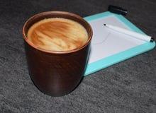 Foto av en kopp kaffe på en bakgrund av ett magnetiskt bräde och tuschpennor En genomdränkt kaffefärg med ett luftigt skum och et arkivbild