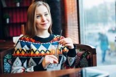 Foto av en kvinna som dricker fruktsaft till och med fönster Arkivfoton