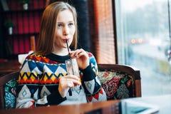 Foto av en kvinna som dricker fruktsaft till och med fönster Arkivbilder