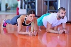 Foto av en kvinna som gör liggande armhävningar i en idrottshall med hennes personliga instruktör Arkivbild