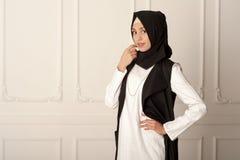 Foto av en mitt för ung kvinna - östligt utseende i den moderna muselmankläderna och den svarta halsduken Arkivbilder