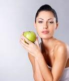 Foto av en ung kvinna med det gröna äpplet. Arkivfoton