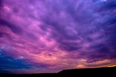 Foto av en violett solnedgång med moln Arkivfoto