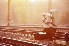 Foto av ett fragment av en järnvägsspår med en liten trafikljus i regnig weathe royaltyfria foton