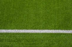 Foto av ett grönt syntetiskt grässportfält med den sh vita linjen arkivbilder