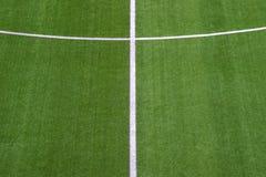 Foto av ett grönt syntetiskt grässportfält med den sh vita linjen arkivfoto