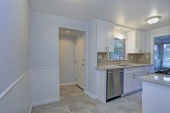 Foto av ett litet kompakt kök med vita shakerkabinetter royaltyfria foton