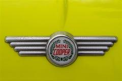 Foto av ett retro emblem för Mini Cooper billogo på en gul Mini Cooper bil royaltyfria bilder